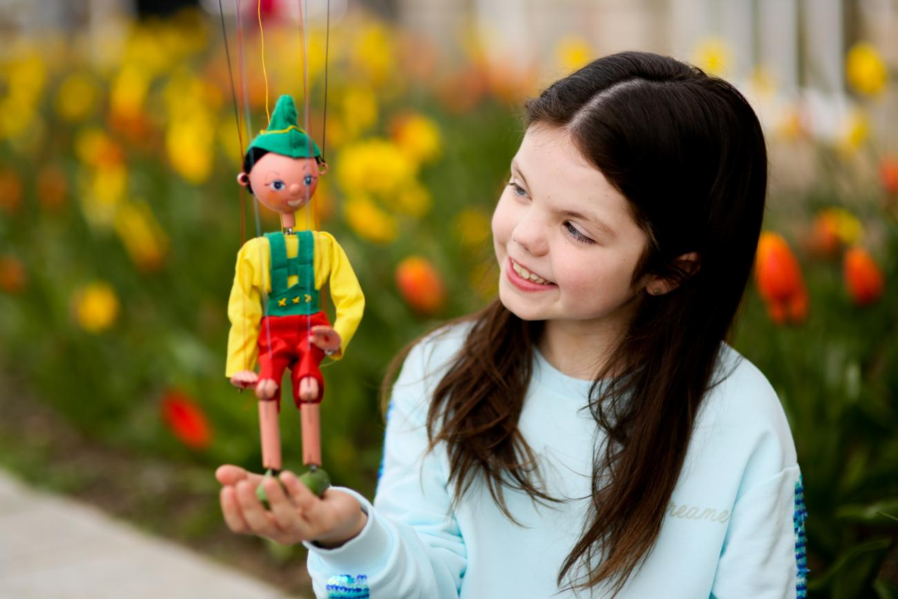A young girls holding a little marionette puppet on her hand.